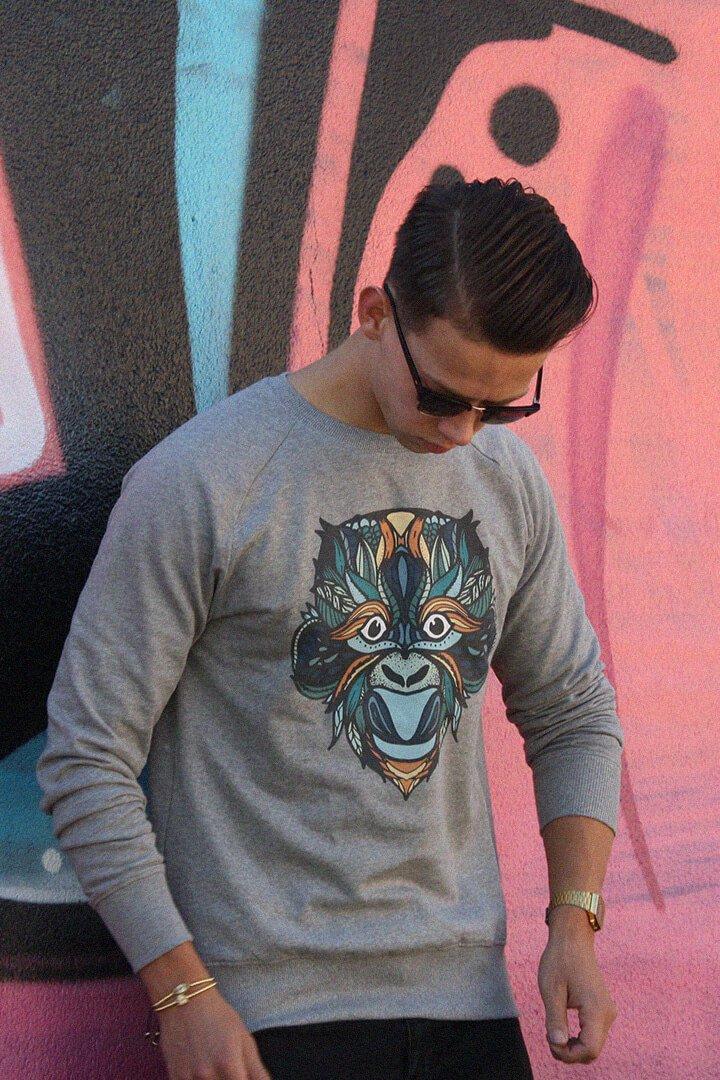 Man met Apenkop trui van ADUH bij graffiti muur